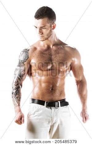 Muscular sexy fitness model posing shirtless over white background. Studio shot of Athletic young man with tattooed torso.