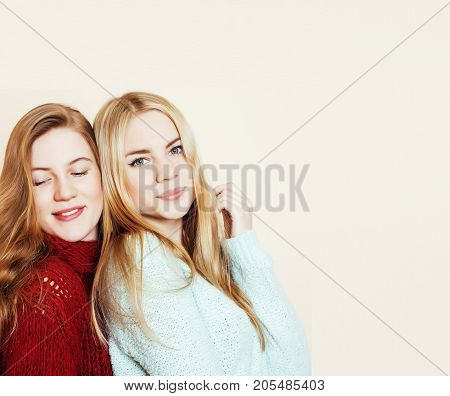 Two young girlfriends in winter sweaters indoors having fun. Lifestyle. Blond teen friends close up smiling