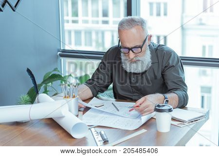 Making everything correctly. Portrait of rofessional bearded engineer sitting at the table and holding pencil while drawing blueprint with concentration. Window on background