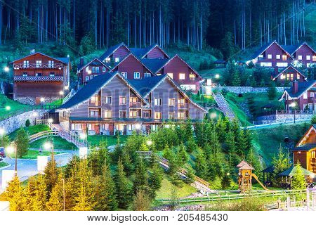 Scenic summer view of winter mountain ski resort with house cottages with forest and skiing in Bukovel, Ukraine