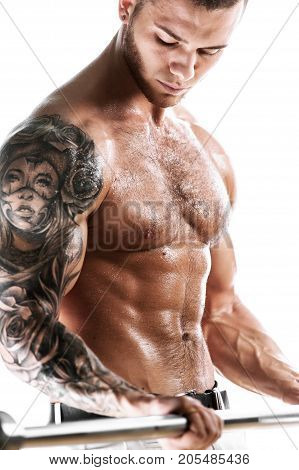 Muscular sexy fitness model posing shirtless over white background. Studio shot of Athletic young man with tattooed torso holding barbell in hands.