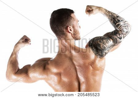 Studio shot of muscular young man posing shirtless, showing biceps muscles. Studio shot of Male fitness model with tattooed shoulder over white background.