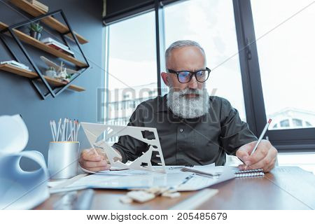 Important task. Low angle portrait of serious gray-haired mature man in glasses is holding plastic stencil and making notes with concentration. He is sitting against window at his working place with blueprints