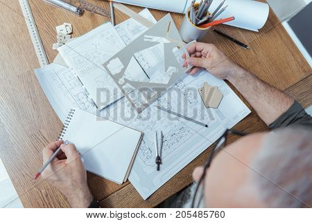 Real professional. Top view of working place of gray-haired old engineer, who is holding plastic pattern and making notes in copybook. Man is sitting at table with building plans, pencils and rulers