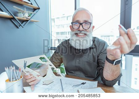 Enjoying work. Cheerful bearded engineer is sitting at table with blueprints and looking at camera with joy. He is expressing happiness while laboring in office on his project. Portrait