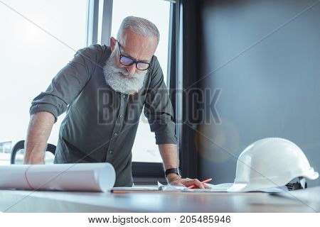 Important job. Portrait of serious bearded engineer is leaning on table and looking at his project with concentration. Safety helmet is on desk. Copy space in the right side