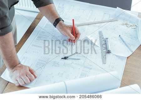 Close-up top view of hands of professional engineer who is working on his project. He is leaning on table and taking notes in blueprint. Copy space in the right side