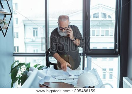 Important call. Pleasant bearded gray-haired engineer is talking on mobile phone while looking at his design plan with concentration. He is standing against big window