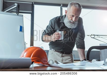 Need some energy. Serious bearded architect is leaning over table and holding coffee cup while looking at design plan with concentration. Safety helmet is on desk. Copy space in the left side