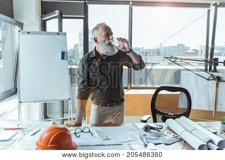 Fresh yourself. Pleasant old stylish architect is leaning on desk and drinking. Blueprints, safety helmet, glasses and other things are on table. Big window with cityscape on background
