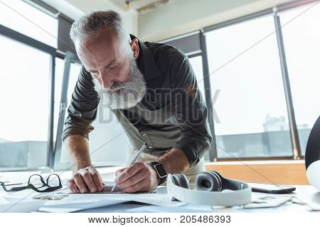 Sense of responsibility. Low angle of qualified old engineer is leaning over table and drawing blueprint. He is looking at his project with concentration. Copy space in the right side