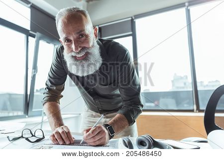 Full of joy. Low angle portrait of cheerful skillful engineer with beard is leaning over table and holding pencil while looking at camera with smile. Copy space in the right side