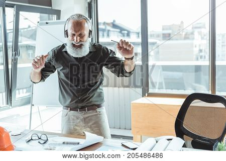 Enjoying song. Joyful elderly bearded man is dancing in office while listening to music through headphones and expressing gladness. He is standing against window with cityscape. Copy space