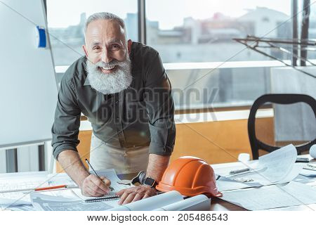 Good mood. Portrait of cheerful bearded engineer is leaning over table and looking at camera with joy while making some notes in notepad. Copy space in the right side