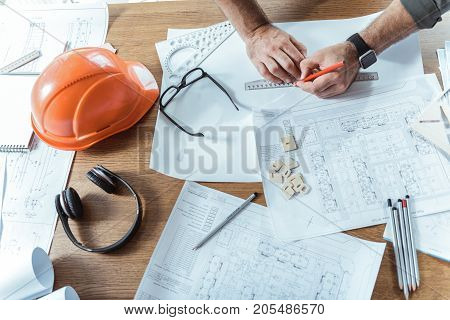 My workplace. Top view close up of wooden table with blueprints, headphones, safety helmet and other things of skillful engineer. He is standing near desk and drawing design plan