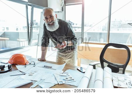 Feeling good. Portrait of confident positive senior bearded man is leaning over table with blueprints and looking at camera with joy. He is standing against big window. Copy space