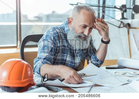Need to think. Positive gray-haired senior engineer is sitting at table and looking at blueprint with concentration. He is touching his head while leaning on desk with safety helmet on it