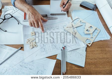 Top view close up of wooden table of qualified engineer. Man is working with blueprints while making notes in notebook. Pencils glasses rulers papers pattern and mobile phone are on desk. Copy space