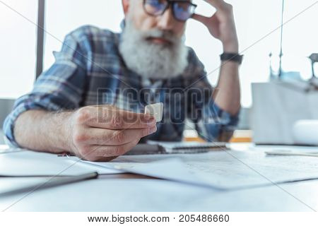 Close-up of hand with sample of senior bearded man in glasses. He is sitting in office and looking at model while leaning on desk and touching his temple. Selective focus
