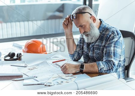 Feeling hopeless. Profile of serious old bearded man is sitting at table and looking at his documents while holding glasses. Blueprints, safety helmet, headphones and pencils are on desk. Copy space