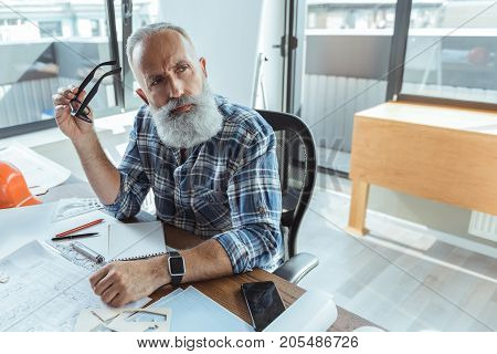 Searching decision. Portrait of professional bearded engineer is sitting at working place and looking aside thoughtfully while holding glasses. Copy space in the left side