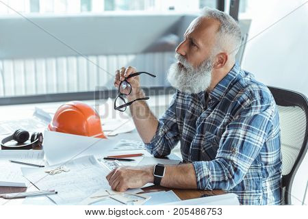 Lost in thought. Profile of qualified old bearded engineer is sitting at table with blueprints and looking aside pensively while holding glasses. Copy space in the left side