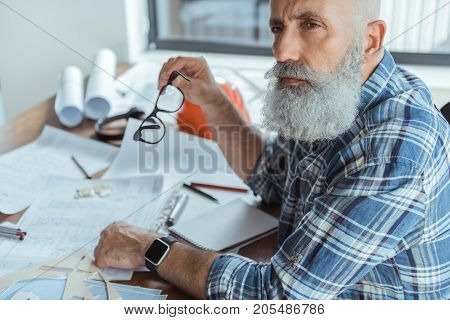Time to think. Pleasant senior bearded engineer is sitting at table with blueprints and looking aside thoughtfully while holding glasses. Copy space in the left side
