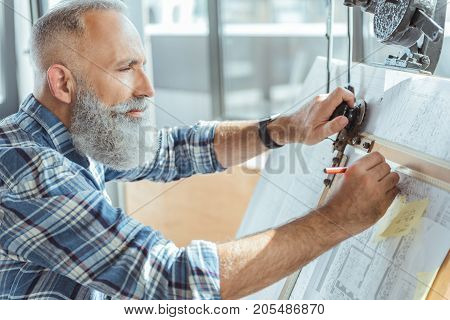 Profile of concentrated bearded senior engineer is using drawing tool for making measurements. He is standing with pencil and taking notes in his blueprint