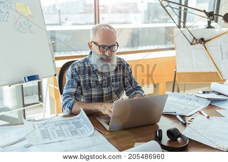 Modern device. Delightful elderly engineer with beard is sitting at table with big window and professional equipment on background and expressing gladness. He is typing on laptop with concentration