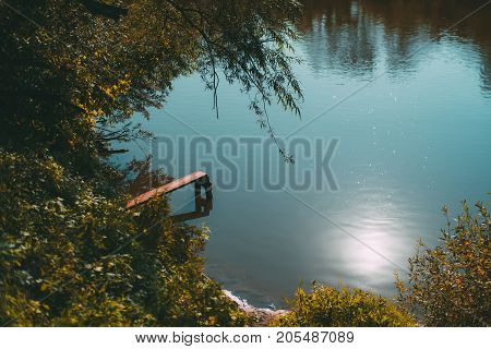 Autumn pond reflecting teal sky with small wooden springboard for jumping into the water; greenery around bushes sludgy riverside trailing tree branches sunny day Russia