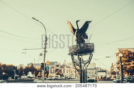 Metal monument of flapping crane or heron near its nest located in the centre of Novosibirsk in Russia in front of museum of local lore road and cars in background vintage color autumn sunny day