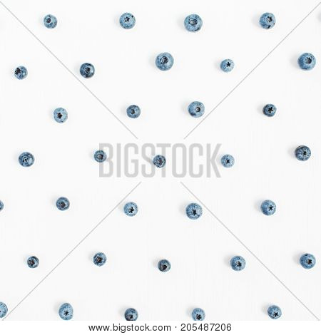 Blueberries on white background. Food blog or magazine concept texture.