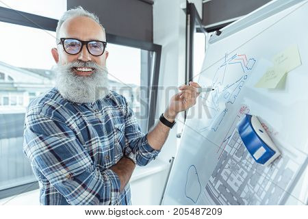 Pleasant job. Portrait of cheerful professional bearded engineer is standing near flip chart with blueprint on it and looking at camera with joy. Copy space in the right side