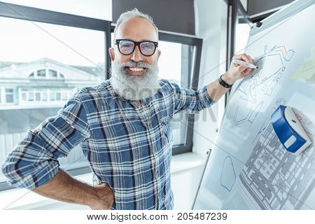 Positive mood. Portrait of delightful elderly bearded engineer in glasses is drawing sample on flip chart while looking at camera with joy. He is standing against window with cityscape