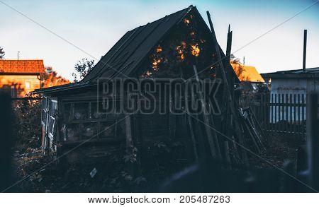 Dark silhouette of abandoned wooden house in holiday village on sunset with strong sun spots on the roof; blue clear sky fencing and other houses in background; decomposed beams leant on facade