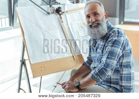 Love my job. Portrait of cheerful bearded engineer is sitting in office with drawing tool and blueprints on background. He is looking at camera with joy. Copy space in the left side