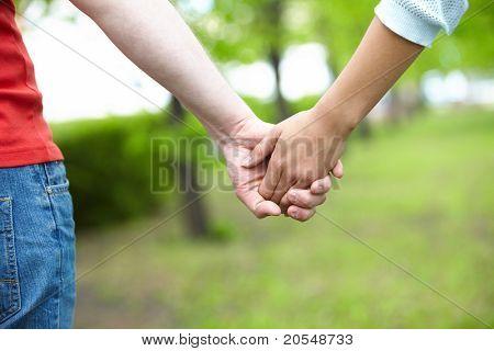 Nahaufnahme der weiblichen und männlichen holding hände im park