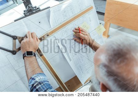 Qualified worker. Top view of skillful elderly gray-haired engineer is drawing design plan using professional equipment. He is holding instrument and making measurements