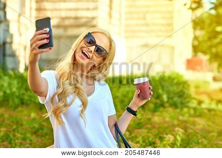 A beautiful young blonde woman standing in the shade next to an old building while holding a coffee and taking a selfie with her smartphone