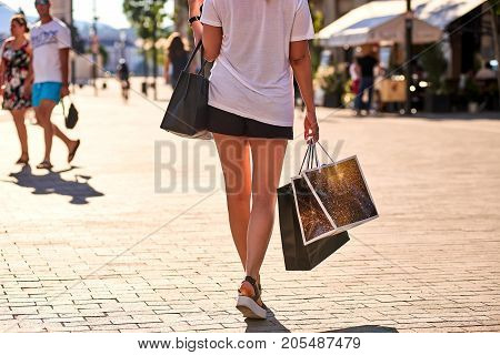 Close up look of paper shopping bags in a young woman hands who is wearing sandals