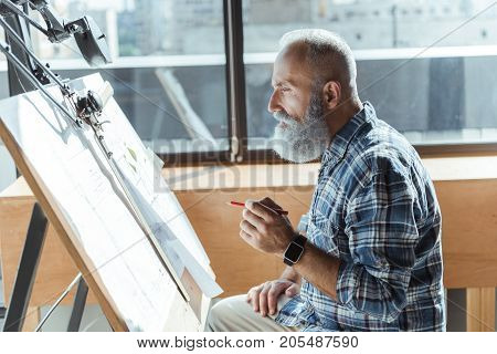 Profile of concentrated professional bearded architect is sitting in front of drawing tool and holding pencil while looking at board thoughtfully. Copy space in the left side