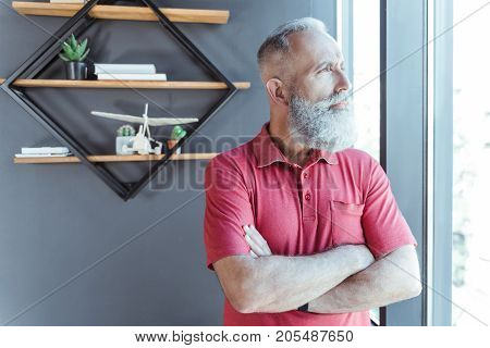 Feeling confident. Pleasant old bearded man is standing near window with crossed arms and looking through glass thoughtfully. Copy space in the left side