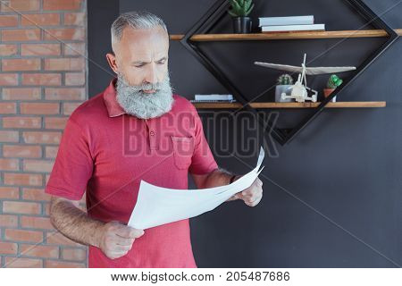 Confident serious bearded businessman is standing in office and holding sheet of paper. He is looking at document with concentration. Copy space in the right side