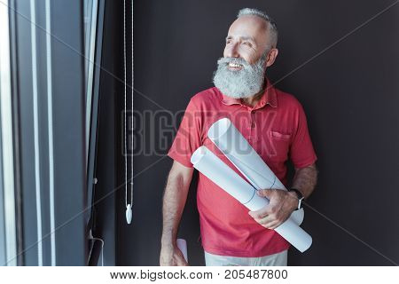 Joyful mood. Smiling gray-haired bearded man is holding blueprints and expressing gladness while looking through window. Copy space in the left side