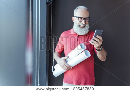 Good news. Cheerful bearded architect in glasses is holding smartphone and looking at screen with smile. He is holding blueprints. Copy space in the left side