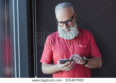 Modern gadget. Delightful senior businessman in glasses is using mobile phone while expressing gladness. He is sharing news with his partners. Copy space in the left side