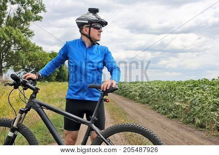 cyclist with Bicycle standing on field path