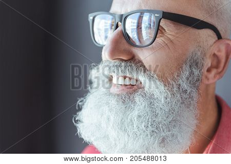 Happiness is my motto. Close-up of face of delightful bearded senior man in glasses. He is looking aside with wide smile. Copy space in the left side