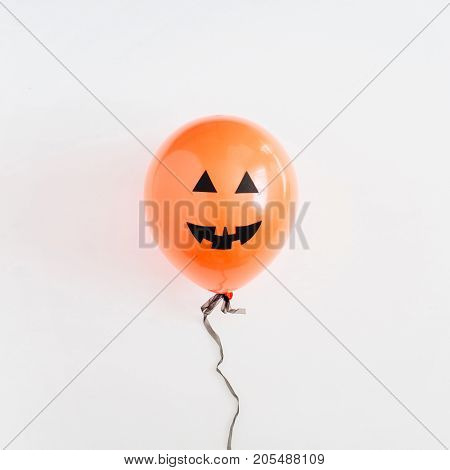 Halloween minimal concept. One orange balloon with funny smiling face on white background. Flat lay top view.