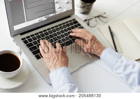 Close up shot of modern woman on retirement doing freelance work using portable electronic device. Elderly female working online on laptop computer at home office selling goods via internet